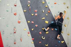 Sporty young woman training in a colorful climbing gym. stock photography