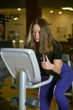 Sporty young woman training on exercise bike Royalty Free Stock Images