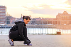 A sporty young woman tying her shoelace Stock Photo