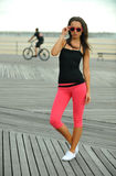 Sporty young woman walking on the boardwalk Stock Images