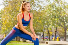 Sporty young woman warming up during workout royalty free stock photography