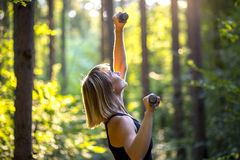 Sporty young woman working out with weights Royalty Free Stock Photos
