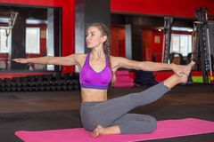 Sporty young woman doing yoga exercises in a gym royalty free stock photo