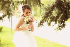 Sposa all'aperto che odora il suo mazzo di nozze Fotografia Stock