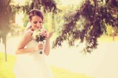 Sposa all'aperto che odora il suo mazzo di nozze Fotografia Stock Libera da Diritti