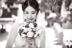 Sposa asiatica felice con i fiori Fotografie Stock