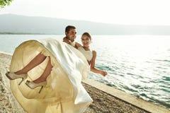 Sposa bella felice della tenuta dello sposo nelle sue armi sulla spiaggia a sunse Fotografia Stock Libera da Diritti