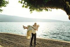 Sposa bella felice della tenuta dello sposo nelle sue armi sulla spiaggia a sunse Immagini Stock