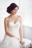Sposa in bello vestito che si siede sulla sedia all'interno fotografie stock libere da diritti