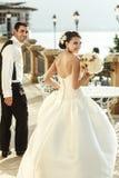 Sposa castana sexy emozionale in vestito bianco che posa al balcone n Immagini Stock