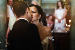 Sposa castana sorridente felice che bacia sposo in vestito nero nel chur Fotografie Stock