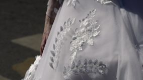 Sposa che cammina in una città ed in un vestito d'ondeggiamento stock footage