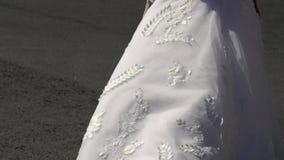 Sposa che cammina in una città ed in un vestito d'ondeggiamento video d archivio