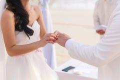 Sposa che dà un anello di fidanzamento al suo sposo sotto il deco dell'arco immagine stock libera da diritti