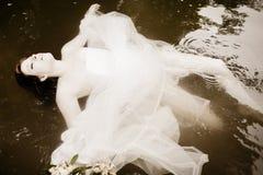 Sposa che galleggia nell'acqua Fotografie Stock Libere da Diritti