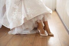 Sposa che mette sulle scarpe di nozze a casa dove sta preparandosi - vestito bianco d'uso in una stanza luminosa con di legno immagine stock libera da diritti