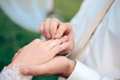 Sposa che mette una fede nuziale sul dito Fotografia Stock
