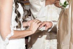 Sposa che mette una fede nuziale sul dito del suo sposo durante la cerimonia di nozze immagini stock libere da diritti