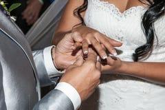 Sposa che mette una fede nuziale sul dito del suo sposo durante la cerimonia di nozze immagine stock libera da diritti