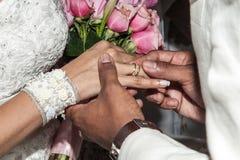 Sposa che mette una fede nuziale sul dito del suo sposo durante la cerimonia di nozze immagine stock