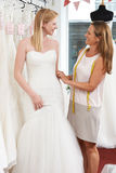 Sposa che è misura per il vestito da sposa dal proprietario di deposito Fotografie Stock Libere da Diritti