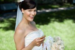 Sposa che per mezzo del telefono delle cellule Fotografia Stock