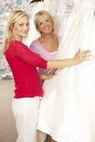 Sposa che prova sul vestito da cerimonia nuziale con le vendite di aiuto Fotografie Stock