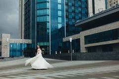 Sposa che si gira davanti all'alta costruzione Fotografia Stock
