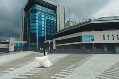 Sposa che si gira davanti all'alta costruzione Immagine Stock Libera da Diritti