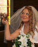 Sposa che si siede in una holding del banco di chiesa della chiesa il suo velare Fotografia Stock