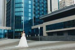Sposa che sta davanti all'alta costruzione Fotografie Stock Libere da Diritti