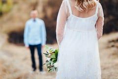 Sposa che sta davanti allo sposo che tiene il mazzo di nozze Fotografia Stock
