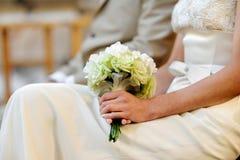 Sposa che tiene i bei fiori di cerimonia nuziale Fotografia Stock