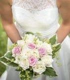 Sposa che tiene i fiori rosa e bianchi di nozze immagini stock