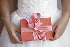 Sposa che tiene il suo contenitore di regalo rosso fotografia stock libera da diritti