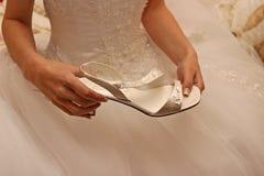 Sposa che tiene la sua scarpa di nozze Immagini Stock Libere da Diritti