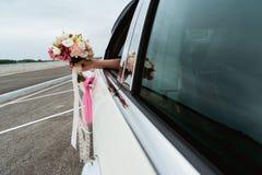 Sposa che tiene mazzo nuziale, dalla finestra di automobile Immagini Stock