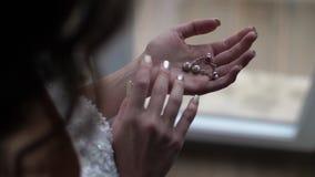 Sposa con capelli lunghi che esaminano l'ornamento che si trova sulla sua palma video d archivio