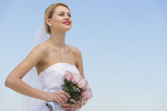 Sposa con il mazzo del fiore che distoglie lo sguardo contro il chiaro cielo blu Fotografie Stock Libere da Diritti