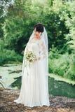 Sposa con il mazzo di nozze nel lago Immagine Stock Libera da Diritti