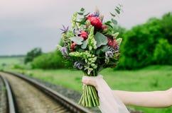 Sposa con il mazzo di nozze in sue mani Il mazzo consiste del lupino, della peonia, del protea, dell'eucalyptus e del loto fotografia stock