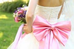 Sposa con l'arco rosa che tiene i suoi fiori immagini stock libere da diritti