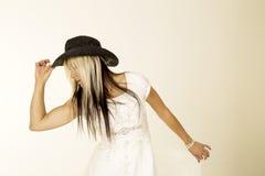 Sposa con lo sguardo del cappello della tenuta del cappello da cowboy alla fine del lato Fotografia Stock