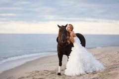 Sposa con un cavallo dal mare Fotografia Stock Libera da Diritti
