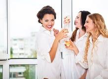 Sposa da essere e bridemaids che giudicano di vetro con champagne Fotografia Stock