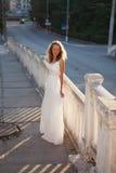 Sposa della giovane donna in un vestito bianco nella città di mattina Fotografia Stock