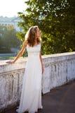 Sposa della ragazza in un vestito bianco vicino alla vecchia palude concreta bianca Fotografia Stock