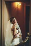 Sposa di Attrective nel fiore bianco e nella posa della tenuta del vestito fotografia stock libera da diritti