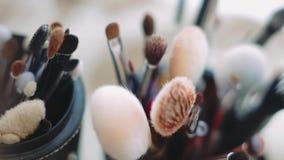 Sposa di mattina Chiuda su delle spazzole, applicatori di trucco Spazzole del nero per trucco Cosmetici di trucco nello spogliato stock footage