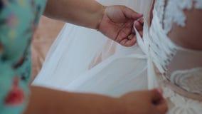 Sposa di mattina Damigella d'onore che lega arco sul vestito da sposa Le mani del ` s della donna allacciano il nastro di seta su stock footage